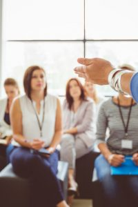 Hand of a trainer addressing group of females sitting in a conference hall. Female hand against defocused group of women attending seminar.
